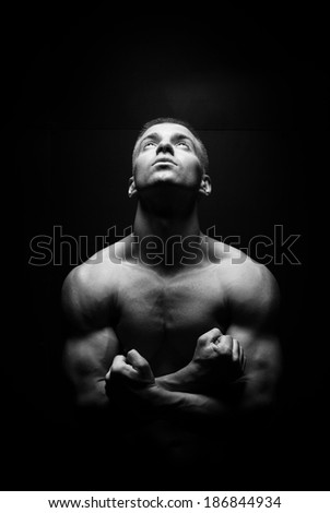young handsome sexy man looking up on a dark background