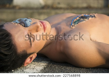 Young Handsome Shirtless Robot Man or Cyborg Dead or Dying in the Street - stock photo