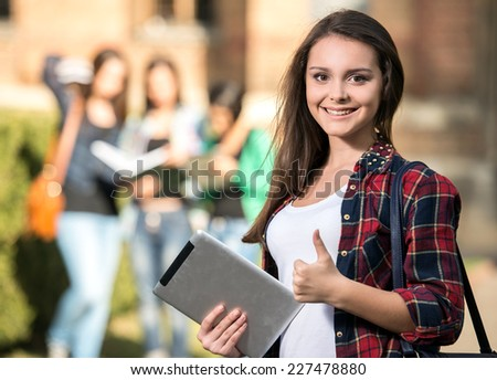 Young handsome, smiling female student at the college, outdoors. Her classmates in the background. - stock photo