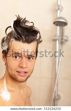Young handsome smiling happy attractive guy taking shower - stock photo