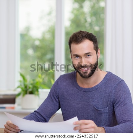 Young Handsome Smiling Man in Navy Blue Gray Long Sleeves Holding White Paper at the Table. Captured Indoor.