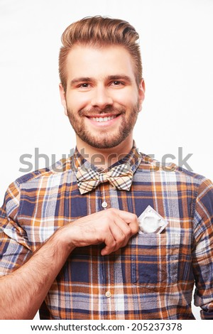 Young handsome smiling man putting a condom into his shirt pocket. Isolated on white background. - stock photo
