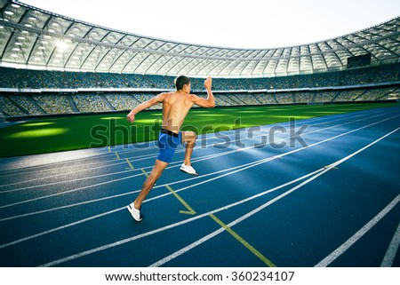 Young handsome sportsman running on racetrack outdoors. Fit sporty man is at large nice modern stadium