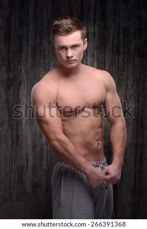 Young handsome sporty well formed man looking at camera and demonstrating muscles. Fitness concept