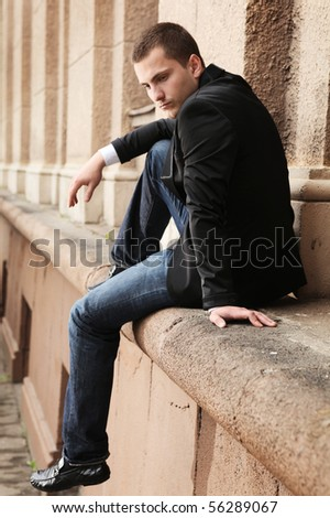 young handsome student sitting near university - stock photo