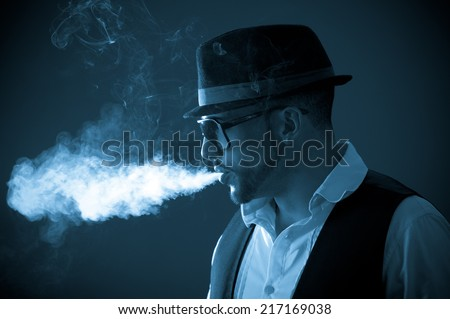 Young handsome stylish bohemian musician male model wearing sunglasses and hat smoking a cigarette color toned