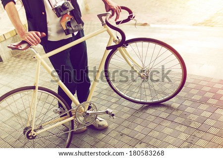 Young handsome stylish hipster man posing on the street with vintage camera and bike on the street in sunny summer day - stock photo