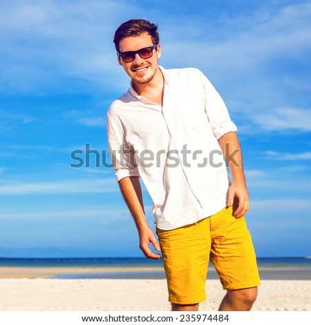 Young handsome stylish hipster man smiling and having fun on amazing tropical beach, wearing bright casual shorts and vintage sunglasses. - stock photo