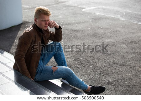Young handsome stylish man in brown jacket in autumn time outdoor in casual style