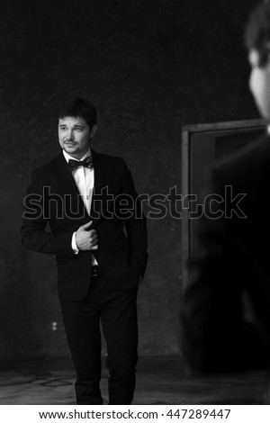 Young handsome stylish man in white jacket and black formal suit with bow-tie standing in interior and posing against mirror