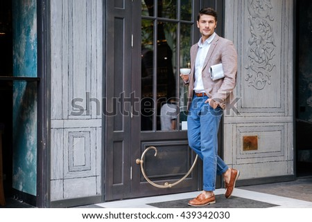 Young handsome stylish man relaxing with cup of coffee outdoors at the cafe - stock photo