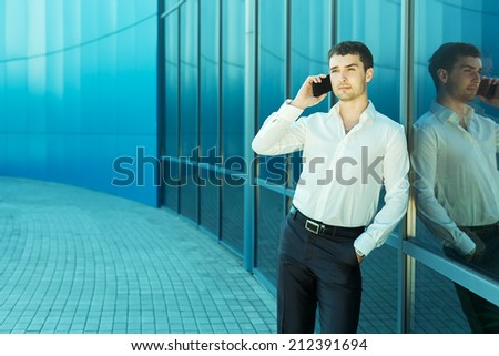 Young handsome successful business man in suit speaking over the phone - stock photo