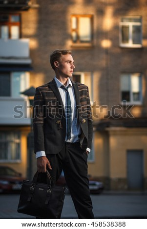 Young handsome successful stylish businessman standing. Concept: victory
