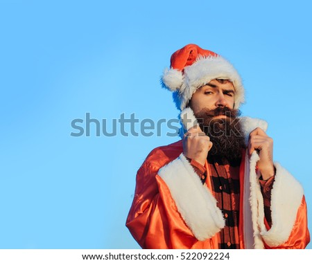 young handsome surprised bearded bad santa claus man with long beard in checkered shirt and red new year hat in christmas or xmas coat outdoor on blue sky background, copy space