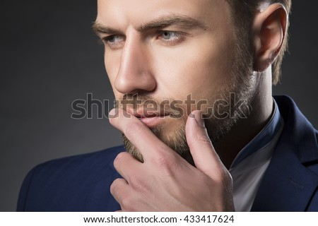 Young handsome thoughtful bearded caucasian man with blue eyes and a hand near chin. Perfect skin and hairstyle. Wearing blue suit. Studio portrait on gradient black to grey background. Toned - stock photo