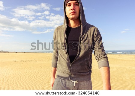 Young handsome tough man walking at beach - Attractive sporty hooded american guy having a break walk along ocean - Portrait of harsh face boxer training outdoor - Concept of people feelings and moods - stock photo