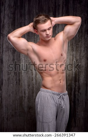Young handsome well formed sporty man demonstrating muscles with his arms raised up. Fitness concept