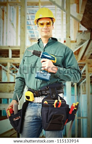 Young handsome Worker man with a drill. Construction.