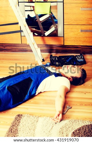 Young handyman fell from a ladder and lies on the floor - stock photo