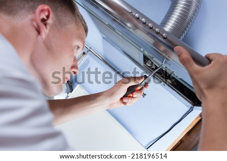 Young handyman fixing a kitchen extractor with a screwdriver - stock photo