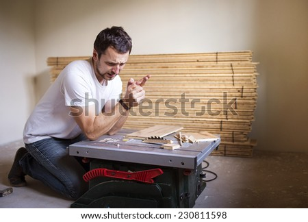 Young handyman having accident during cutting plywood on circular saw - stock photo