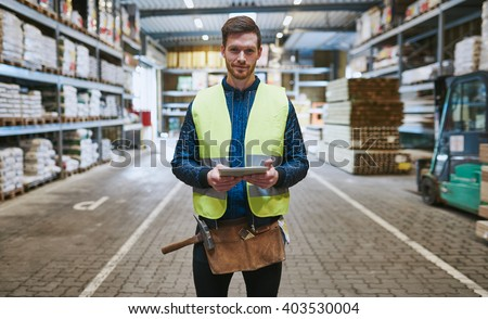 Young handyman or builder standing in the drive through in a hardware warehouse with a tablet in his hand looking at the camera - stock photo