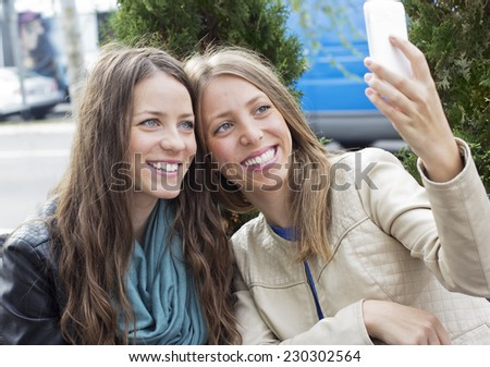 Young happiness woman sitting in the cafe looking at smart phone and and making photography outdoors. - stock photo