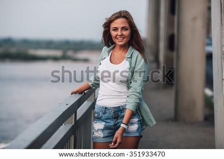 young happy adult beautiful  fashion woman walking on bridge  - stock photo