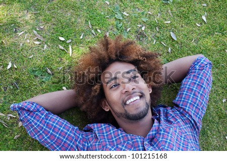 young, happy african american male lying in grass - stock photo