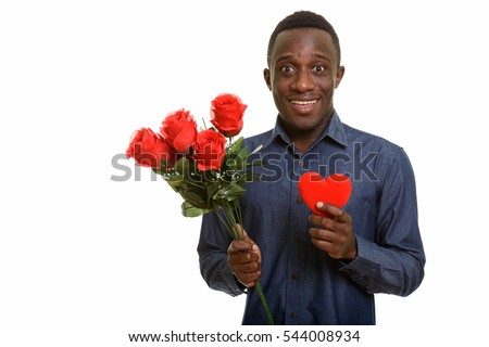 Young happy African man smiling while holding red roses and red heart on chest ready for Valentine's day isolated against white background