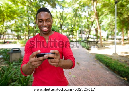 Young happy African man using mobile phone in park at Bangkok city