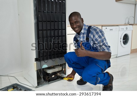 Young Happy African Technician In Uniform Fixing Refrigerator In Kitchen Room - stock photo
