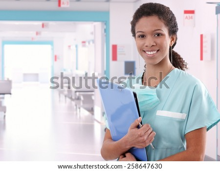 Young happy afro american nurse standing at hospital ward with clipboard and pen in hand. Smiling, looking at camera. - stock photo