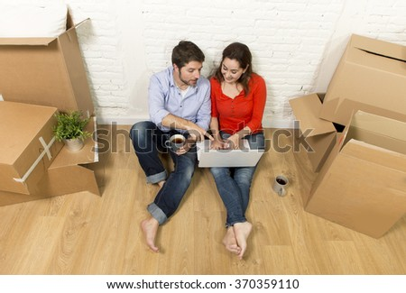 young happy American couple sitting on floor moving in a new house or apartment flat using computer laptop choosing online furniture and household in real estate and independent lifestyle concept - stock photo