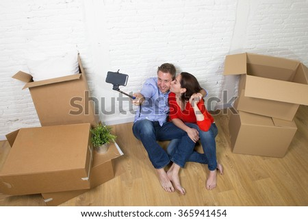 young happy American couple sitting on floor unpacking boxes together celebrating  moving in a new house or apartment flat taking selfie photo in real estate concept