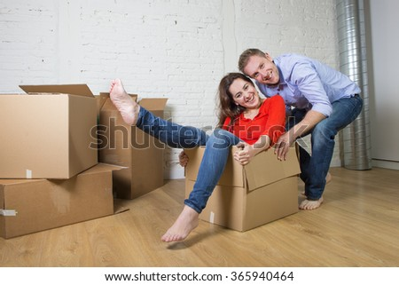 young happy American couple unpacking having fun enjoying together moving in a new house or flat playing with woman or wife inside cardboard box and husband or boyfriend pushing in real estate concept