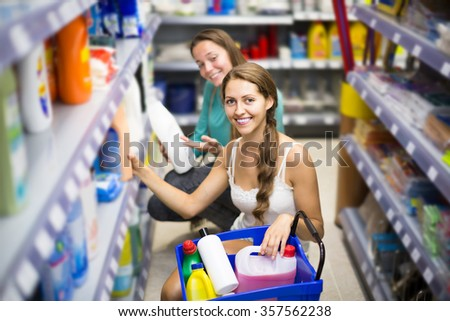 Young happy american  people choose some detergents in the shop   - stock photo