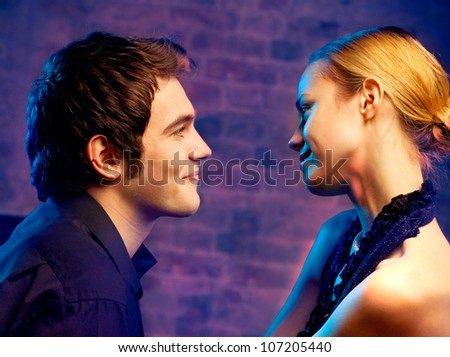 Young happy amorous attractive couple looking at each other, at club