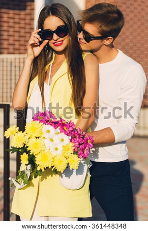 Young happy amorous cheerful couple with  flowers, outdoor.  Young pretty girl and her handsome boyfriend embracing  and enjoying  time  together.  Warm sunny colors.  - stock photo