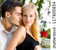 Young happy amorous cheerful couple with rose, outdoor - stock photo