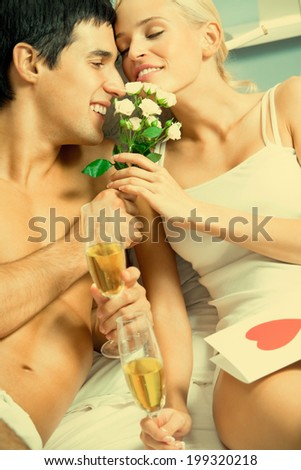 Young happy amorous couple celebrating with champagne at bedroom - stock photo
