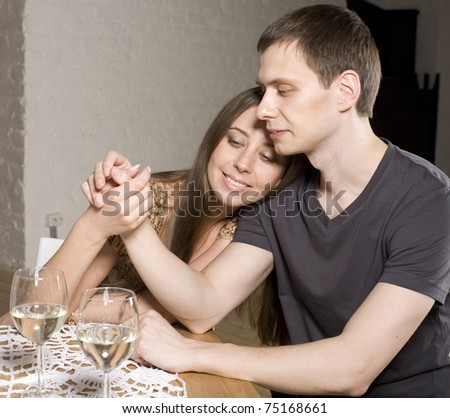 Young happy amorous couple celebrating with white wine at restaurant - stock photo