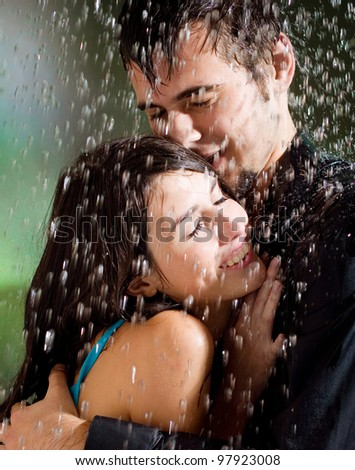 Young happy amorous couple hugging under a rain, outdoors