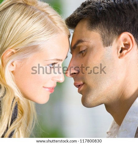 Young happy amorous couple kissing, outdoor - stock photo