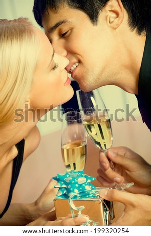 Young happy amorous couple with champagne and gift, kissing at party - stock photo