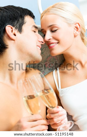 Young happy amorous couple with champagne at bedroom