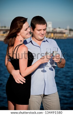Young happy amorous couple with glasses of champagne on blue sky background - stock photo