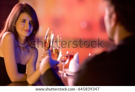 Young happy amorous couple with glasses of champagne on romantic date at restaurant. Love, party and dating concept.