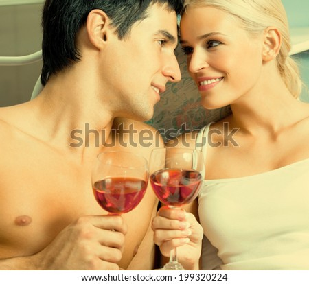 Young happy amorous couple with redwine at bedroom - stock photo