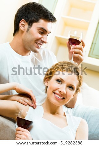 Young happy amorous couple with redwine at home. Love, relations, holidays, romantic concept shot.